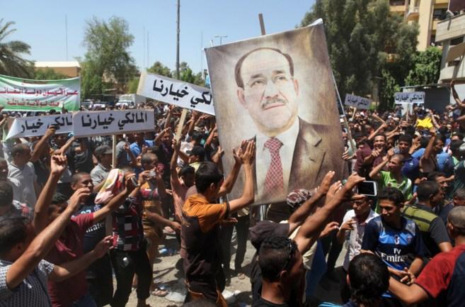 Iraquíes sostienen un retrato gigante de Nuri al Maliki durante una...