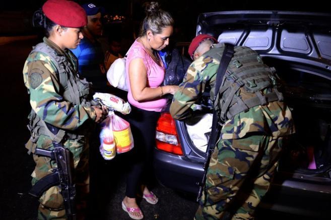 Varios soldados venezolanos inspeccionan el coche de una mujer