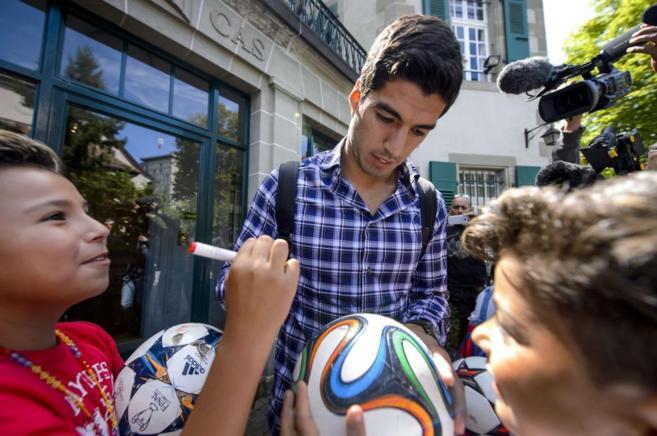 Luis Suárez firma unos balones tras salir de su reunión con el TAS.