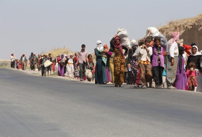 Familias de desplazados yazidíes dirigiéndose a la frontera con...