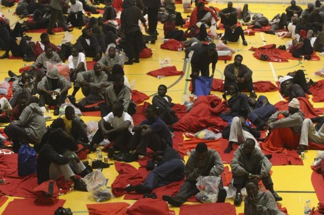 Inmigrantes hacinados ayer en uno de los polideportivos de Tarifa.