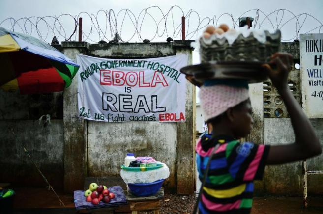 Una chica pasa por delante de un cartel contra el ébola en un...