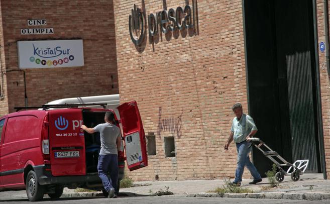 Una furgoneta de Prescal carga objetos que varias personas sacan del...