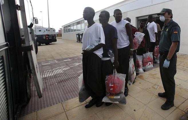 Varios inmigrantes son trasladados ayer desde uno de los...
