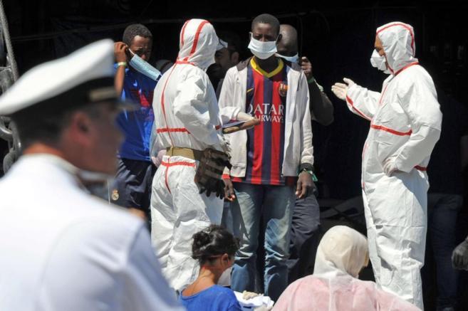 Varios inmigrantes, de un grupo de 1.700 personas, son recibidos por...
