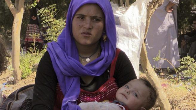 Una madre con su hijo, de etnia yazidí, en un campo de refugiados de...