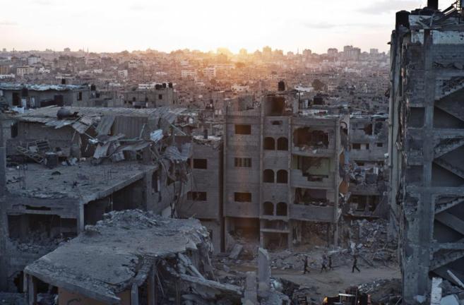 Niños palestinos caminan a través de edificios destruidos durante la...