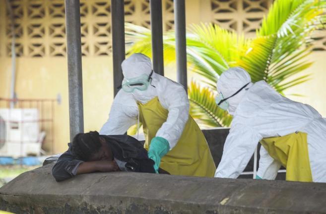 Dos doctores, con ropa especial, atienden a una persona en el hospital...