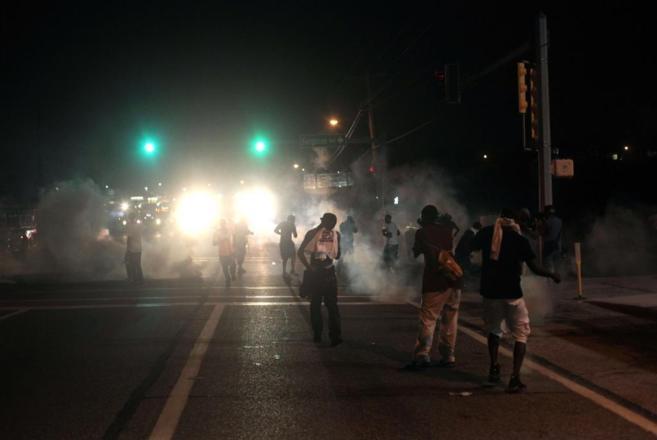 Varios manifestantes se retiran tras lanzar la policía gases...