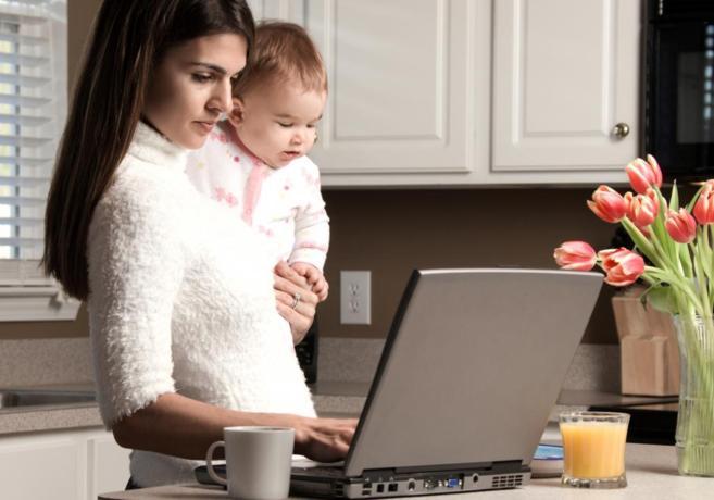 Una mujer trabaja en un ordenador portátil en su casa, con su hijo en...