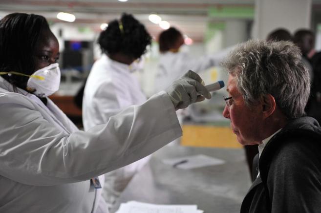 Sanitarios toman la temperatura de los viajeros a su llegada al...