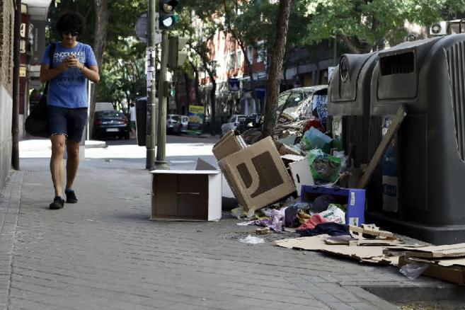 Contenedores y papeleras llanas de suciedad y basura en las calles de...