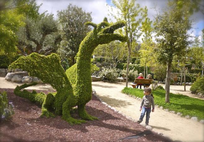 Una niña mira impactada la figura de un dragón de cuatro metros de...