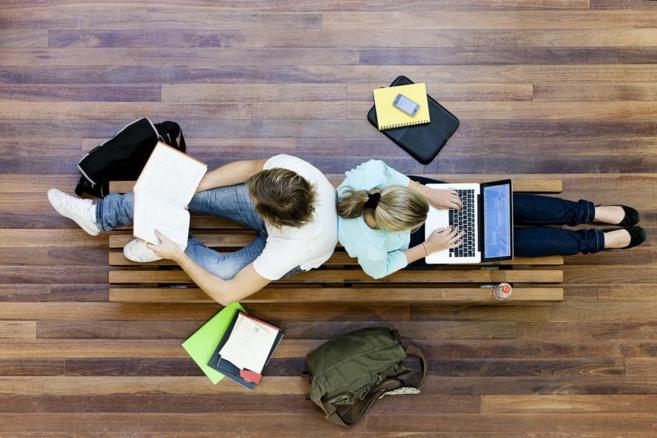 Dos jóvenes estudian con libros y ordenador en una universidad.