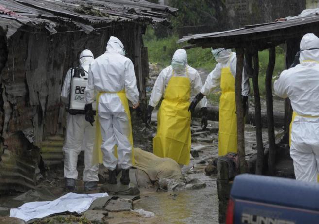 Un grupo de especialistas rodea el cuerpo de un muerto a causa del...