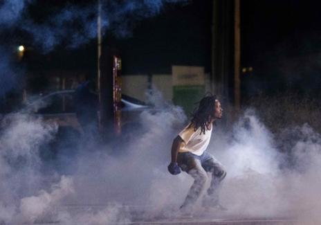 Un manifestante entre el gas lacrimógeno lanzado por la policía.