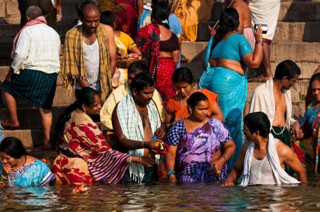 Un grupo de personas se sumergen en el río Ganges.