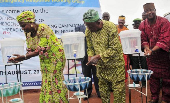 La ministra nigeriana Sarah Ochee (i) se lava las manos como parte de...
