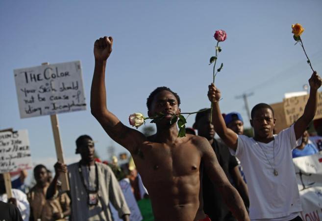 Manifestantes portan carteles y rosas durante las protestas en...