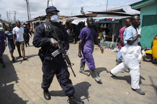 Un soldado liberiano vigila mientras unos enfermeros se dirigen a...