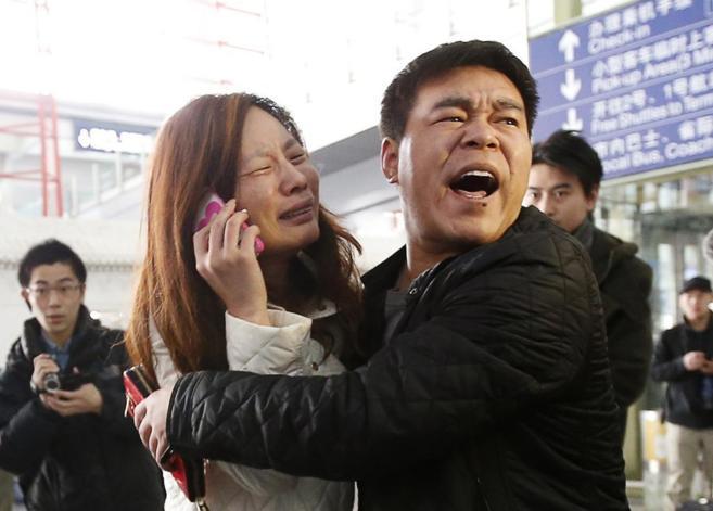 Familiares de pasajeros del vuelo desaparecido lloran en el aeropuerto...