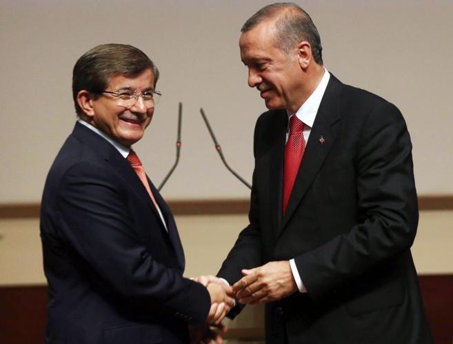 Ahmet Davutoglu y Tayyip Erdogan se estrechan la mano.