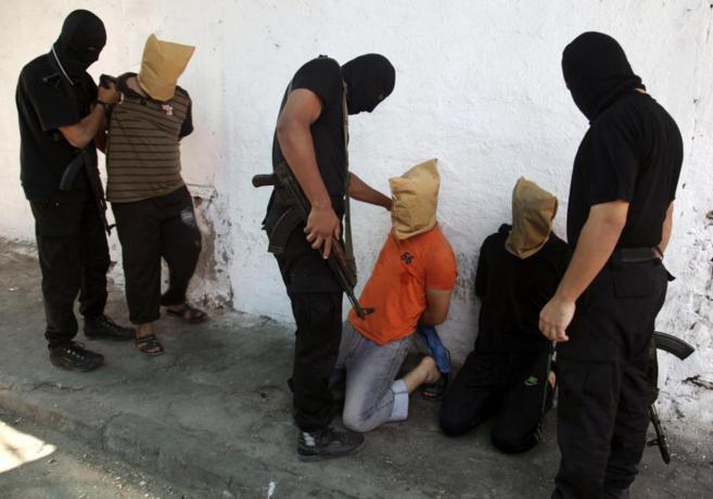 Miembros de Hamas preparan a los supuestos colaboracionistas para su...