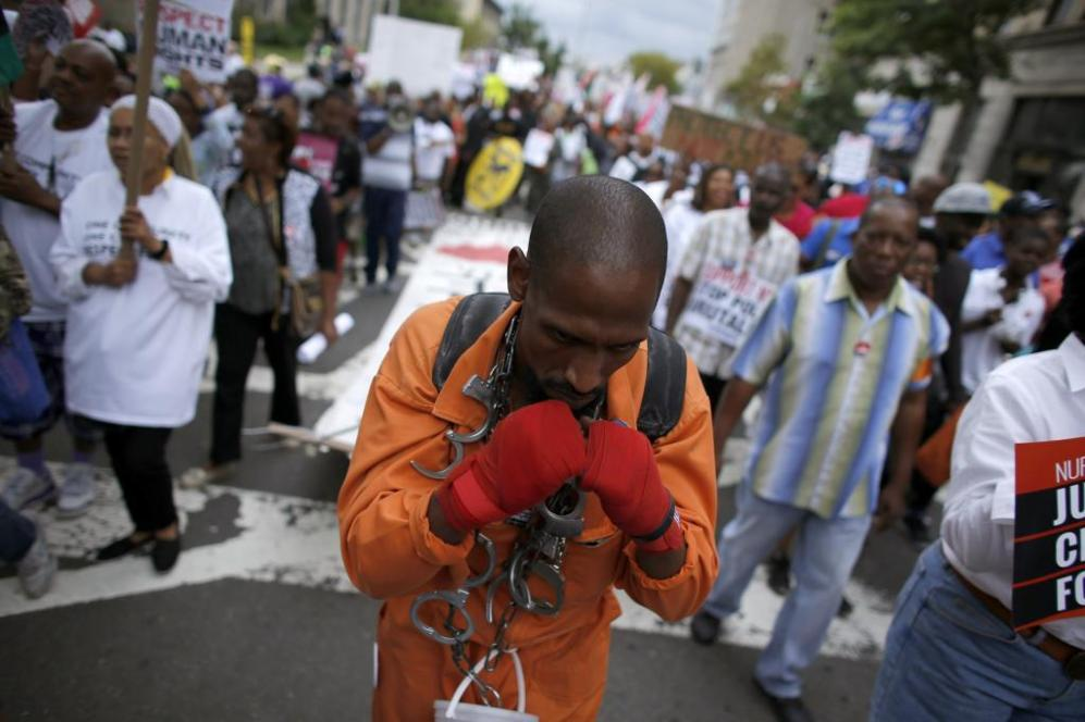 Un hombre cargado de esposas durante la marcha.