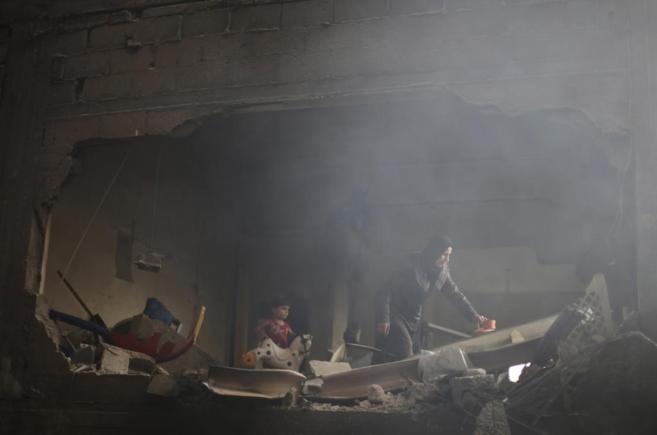 Una mujer palestina rebusca entre los escombros de lo que antes era su...