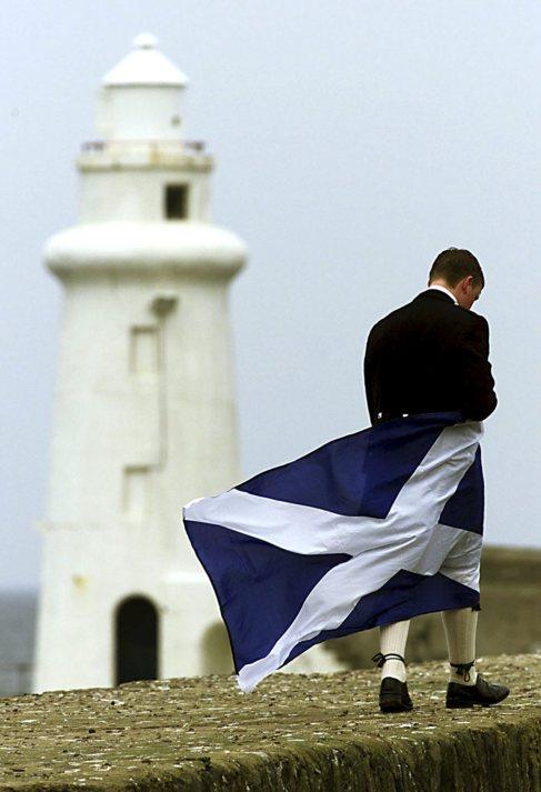 Un hombre camina con el traje típico escocés y una bandera de...