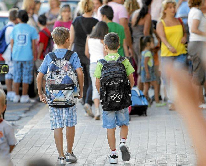 Dos niños caminan hacia el colegio el primer día de clase.