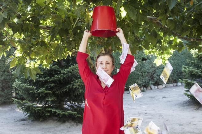 Maite Solas, con un cubo lleno de billetes de euro vertido sobre su...