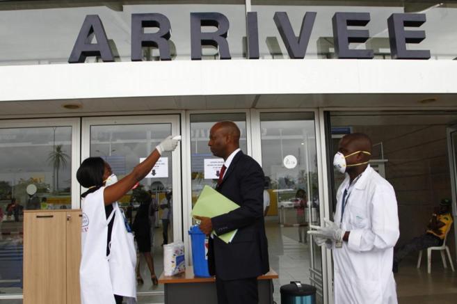 Trabajador de salud de Costa de Marfil toma la temperatura de un...