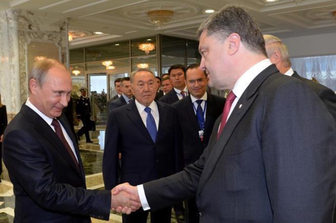 Putin (izda.) y Poroshenko se dan la mano en Minsk.