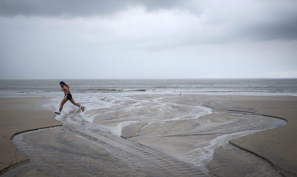 Un hombre corre por la playa frente al mar Arábigo con nubes de...