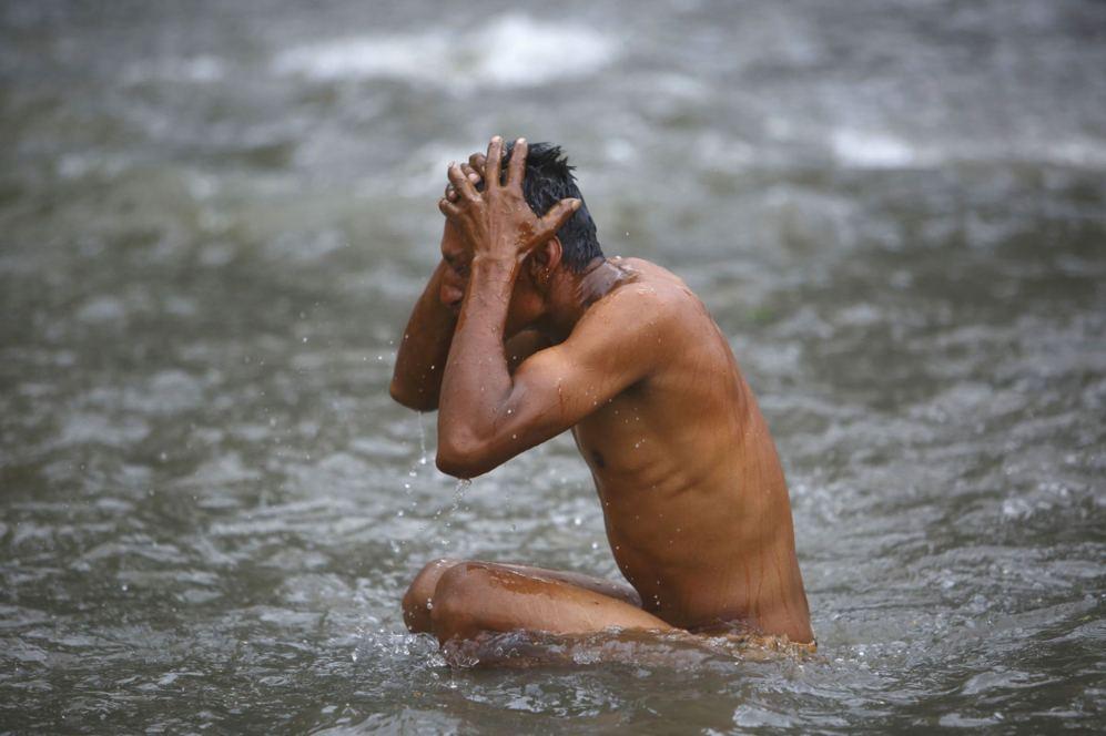 Un devoto hindú se lava después de realizar los rituales en el río...