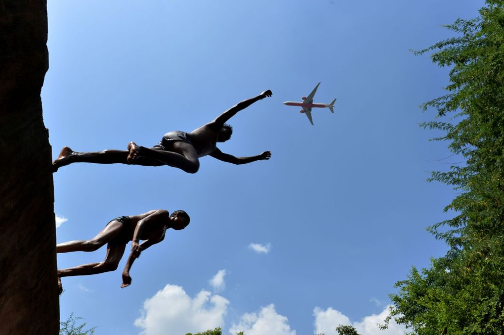 Un avión vuela por encima mientras   jóvenes saltan al agua en...