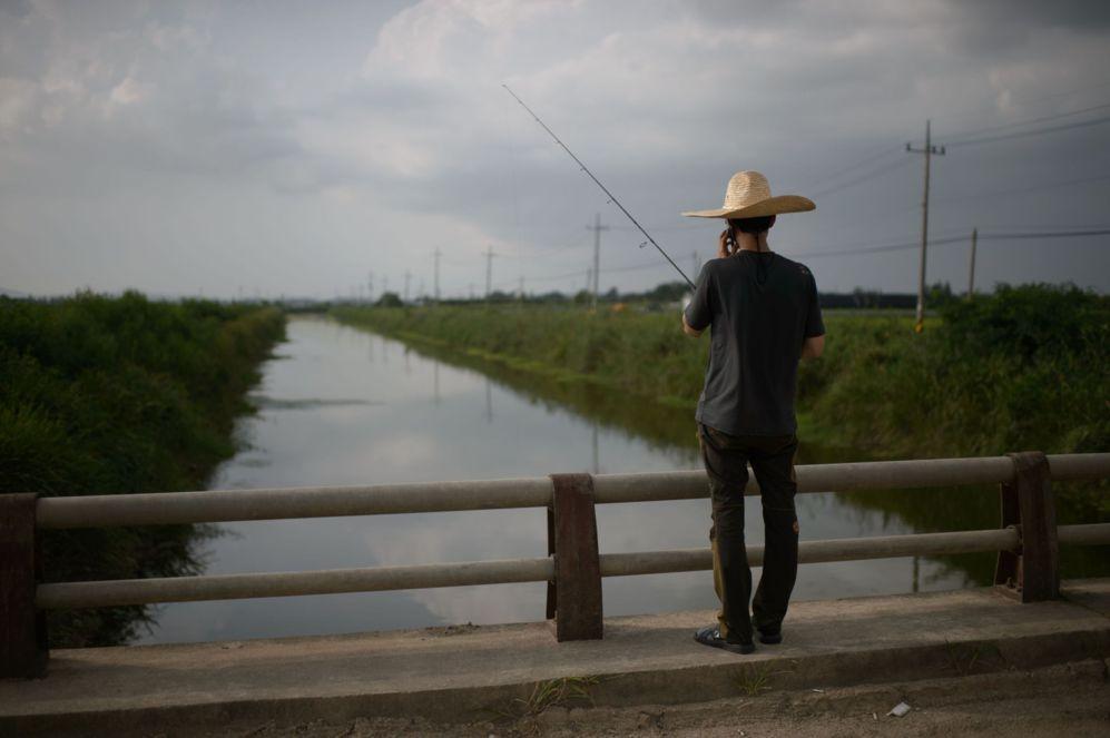 Un pescador habla por un teléfono móvil mientras está de pie frente...