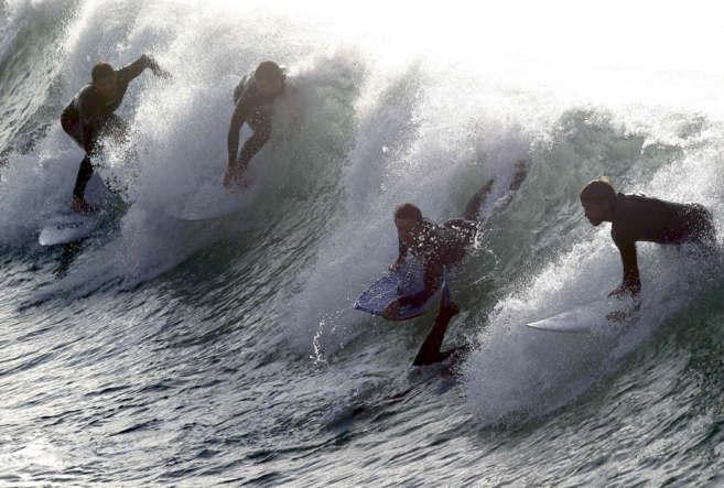 Numerosos surfistas compiten por una ola en la playa de La Zurriola de...
