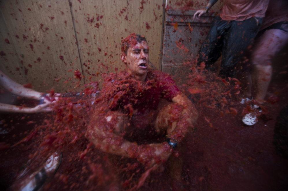 Uno de los participantes en la Tomatina 'atacado' con restos...