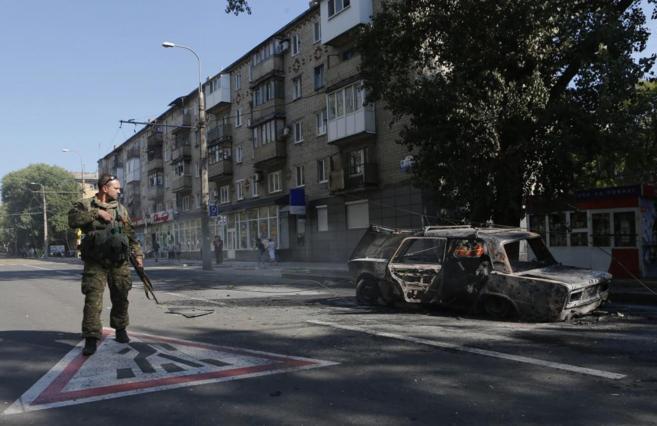 Un soldado pasa delante de un coche quemado en Donetsk.