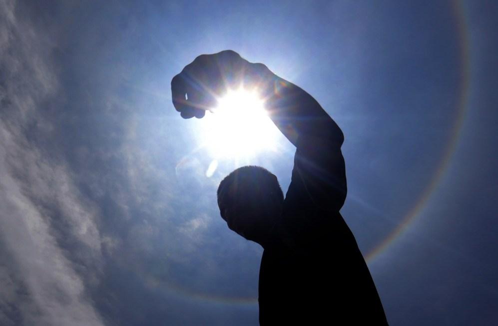 Un hombre se encuentra en el centro de un arco iris que rodea al sol...