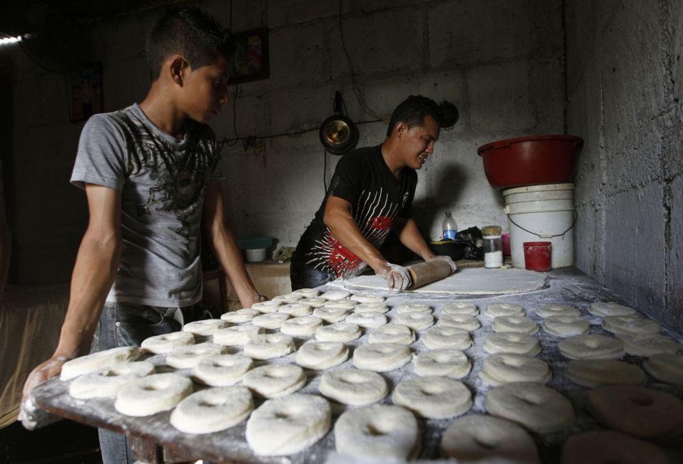 Dos hombres fabrican rosquillas en una casa qeu hace las veces de...