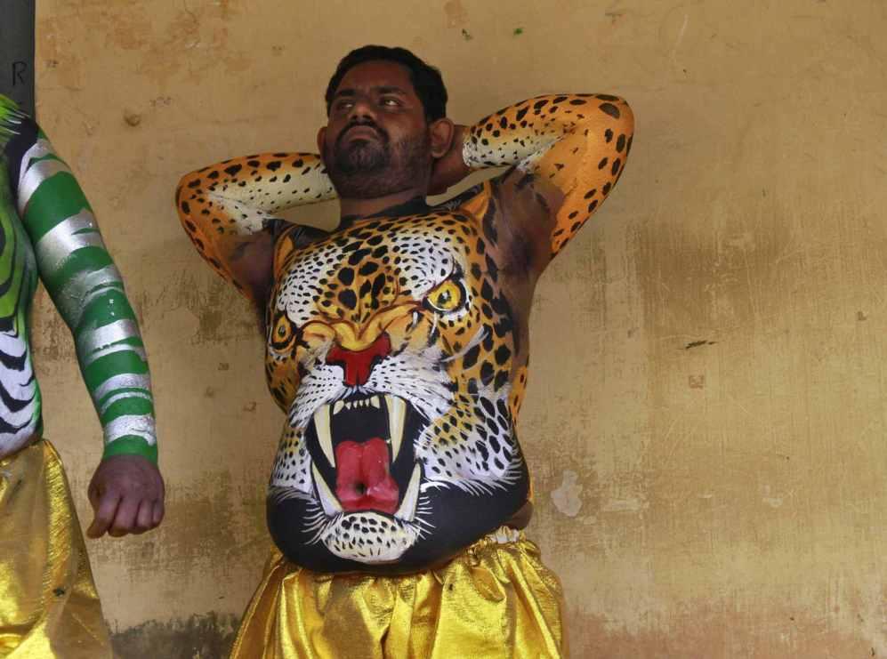 Un bailarín con el cuerpo pintado espera su turno para actuar en el...