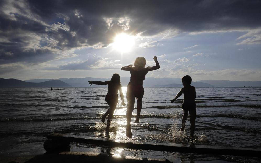 Niños juegan en el lago Prespa, para refrescarse en un caluroso día...