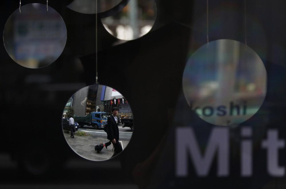 Un hombre se refleja en el espejo de un escaparate en la calle Ginza,...