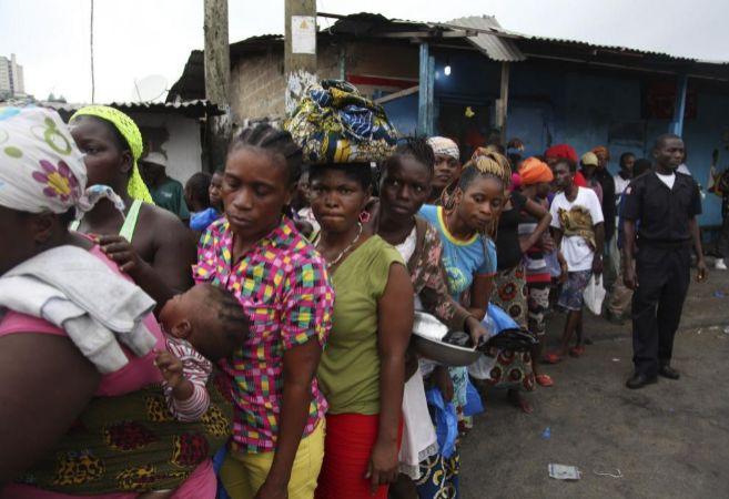 Liberianos esperan la comida que distribuye el Gobierno como parte del...