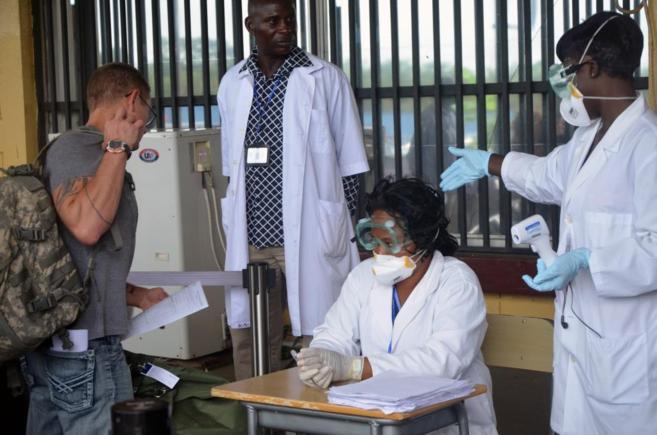 Sanitarios evalúan a un pasajero que va a salir del aeropuerto...