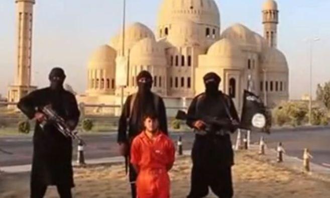 Miembros del IS, momentos antes de ejecutar al soldado kurdo, junto a...