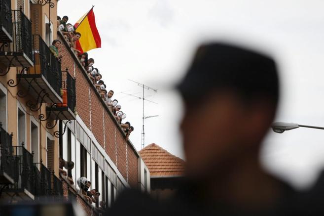 Los neonazis, algunos con caretas, asomados a la ventana del edificio.